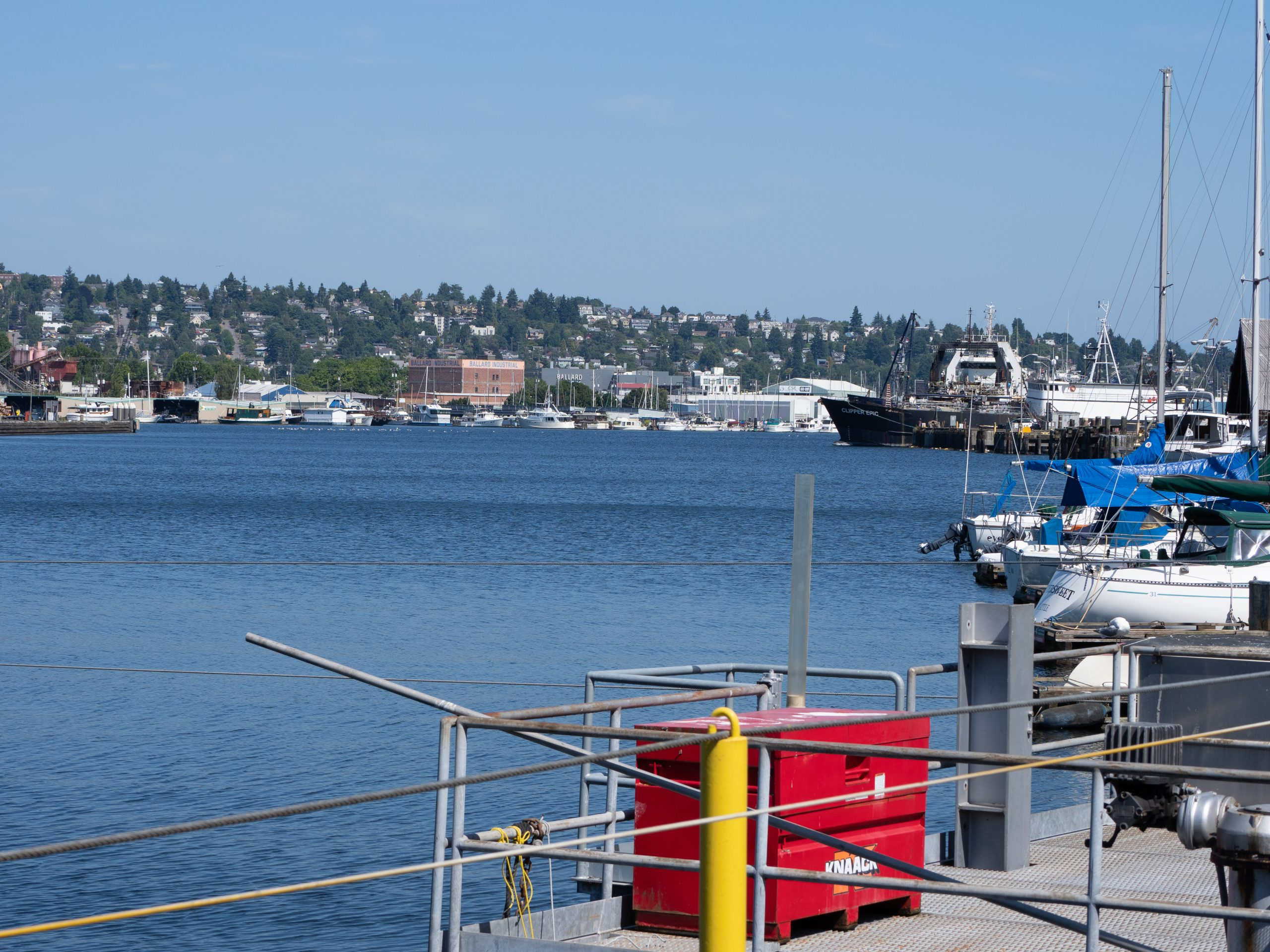 Image is a view across the Lake Washington Ship Canal from a platform with metal railings and a red metal box, looking over several docked sailboats and fishing vessels towards trees, buildings, and boats on the opposite shoreline.