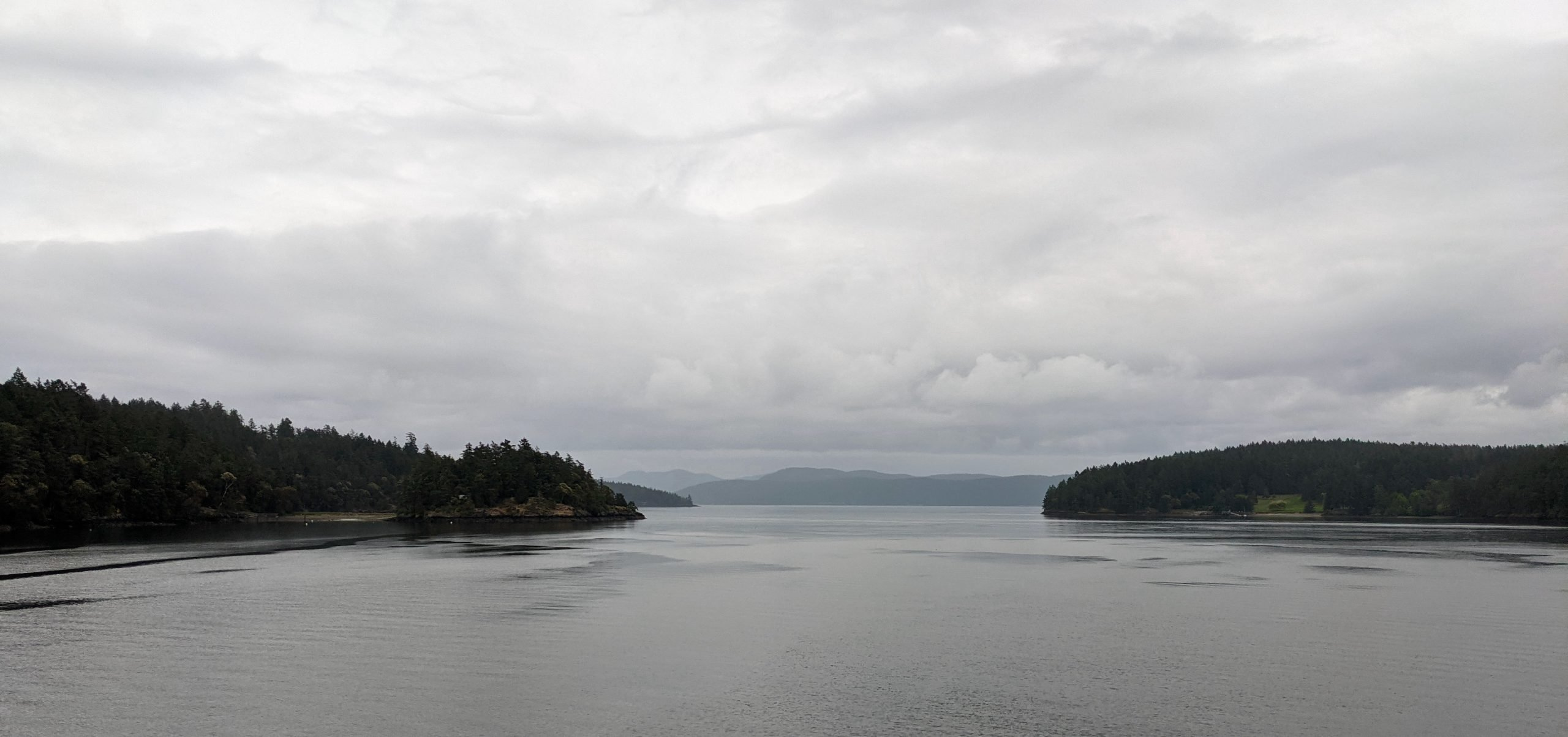 Photo of a wide, grey body of water narrowing to a channel in the center between two green tree-covered land masses. Behind them in the distance are more hills and a cloudy sky.